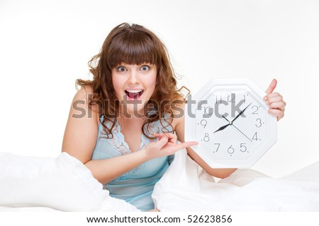 amazed woman sitting in white bed and pointing at clock