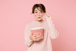 Amazed young brunette woman 20s wearing knitted casual sweater glasses watching movie film, hold bucket of popcorn isolated on pastel pink background. People emotions in cinema, lifestyle concept.