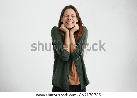 Amazed young female with straight dark hair closing her eyes and clenching fists with pleasure having broad smile being happy to have holidays and to have chance travel abroad. Body language concept #662170765