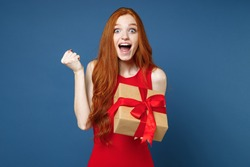 Amazed young redhead girl in red elegant evening dress hold present box with gift ribbon bow doing winner gesture isolated on blue background. St. Valentine's Day Women's Day birthday holiday concept