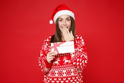 Amazed young Santa woman in sweater Christmas hat hold gift certificate covering mouth with hand isolated on red colour background, studio portrait. Happy New Year celebration merry holiday concept