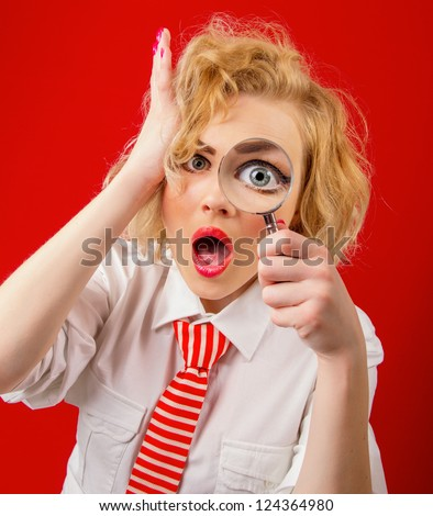 Amazedly funny woman with magnifier, isolated on red background