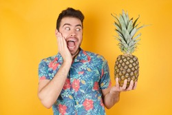 Amazement - man excited looking to the side hand on face and holding a pineapple. Surprised happy young man looking sideways in excitement. Caucasian male model on yellow background.