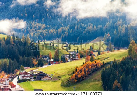 Amazing aerial autumn view on alpine town, sunlit meadows under low clouds. Location place: Santa Maddalena (Santa Magdalena), South Tyrol, Dolomite Alps, Italy.