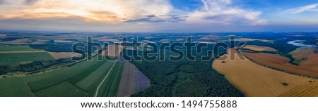 Amazing Aerial panorama from a drone of plowed and green fields, trees at sunset, agriculture concept. Countryside farmland in the summer. #1494755888