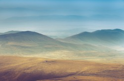 Amazing aerial view of desert,  stone hills, and distant mountains layers range.Wilderness background. Vintage toning effect. Near Mount Erciyes. Kayseri, Turkey.