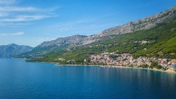 Amazing aerial view of Makarska riviera, Dalmatia, Croatia. Daytime landscape of popular tourist resort on the Adriatic sea coast at the foot of the rocky Dinara mountains, outdoor travel background