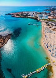 Amazing aerial view over one of the best beaches in Protaras, Cyprus. Yellow sand, blue and turquoise water - perfect summer getaway, luxury vacation in Mediterranean