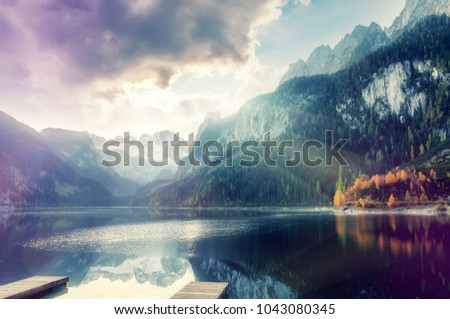 Amazing Alpine valley in Austrian Alps at Sunny day. Incredible Autumn Landscape with famous Lake Gosausee, and Dachstein glacier on background. Top Popular place for photographers and travelers