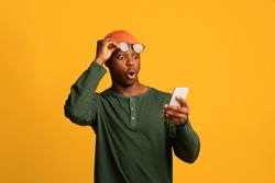 Amazing App. Shocked African American Guy Looking At Smartphone Screen, Amazed Black Millennial Man Taking Off Eyeglasses While Reading Unexpected Message, Standing Over Yellow Background, Copy Space