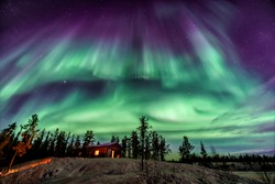 Amazing Aurora in purple and blue color dancing over chalet in Yellowknife