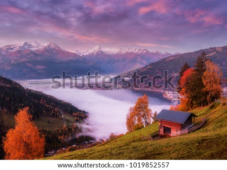 Amazing Autumn landscape on pink sunset. alpine farmland, pasture and high rocky mountains in background, Zell am See lake. Scenic View Of Zeller Lake and Tyrol Alps, Austria, Europe. Cretive image.