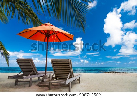 Amazing beach in Maldives. Relaxing blue sky and white sand. Wooden sun beds with sun umbrella. Inspirational luxury travel holiday background concept. #508715509