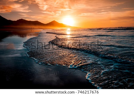 Amazing beach sunset with endless horizon and lonely figures in the distance, and incredible foamy waves. Volcanic hills in the background in idyllic warm colors. #746217676