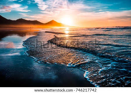 Amazing beach sunset with endless horizon and lonely figures in the distance, and incredible foamy waves. Volcanic hills in the background.