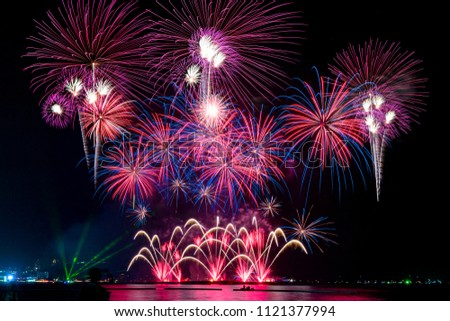 Amazing beautiful colorful fireworks display on celebration night, showing on the sea beach with multi color of reflection on water #1121377994