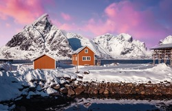 Amazing beautiful nature landscape  of Lofoten Islands. Amazing winter scenery with snow covered mountains pink colorful sky and tipical red fishing huts, rorbu during sunset. popular travel location
