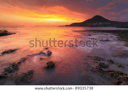 Amazing beautiful sunset reflection on the sea with rock, wave and mountain