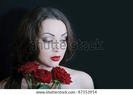 Amazing beautiful woman holding claret-colored roses on the black background