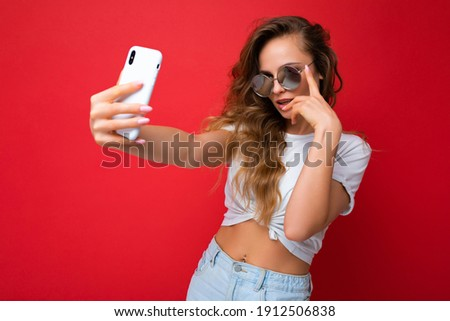 amazing beautiful young blonde woman holding mobile phone taking selfie photo using smartphone camera wearing sunglasses everyday stylish outfit isolated over colorful wall background looking at