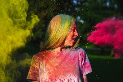 Amazing blonde girl playing with pink and yellow dry paint at the summer Holi Festival