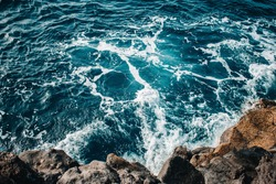 amazing blue turquoise ocean water waves and black rocks