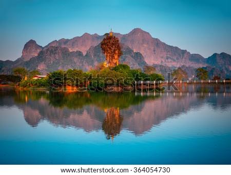Amazing Buddhist Kyauk Kalap Pagoda under evening sky. Hpa-An, Myanmar (Burma) travel landscapes and destinations Stock fotó ©