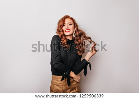 Amazing caucasian girl with long ginger hair posing with smile. Studio shot of carefree graceful woman in black blouse. #1259506339