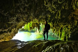 amazing cave with lake and woman admiration