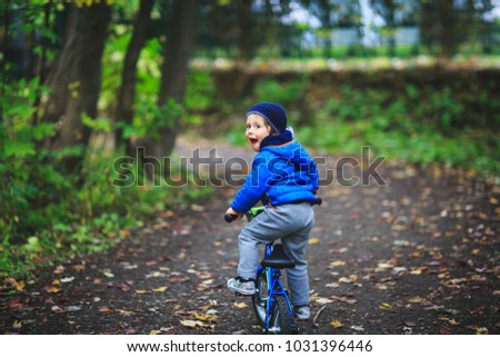 Amazing child on a bicycle at forest road. Child has fun with bicycle. Cute child learning to ride bicycle. Adorable child having fun on his first bicycle. Best pictures for children concept.