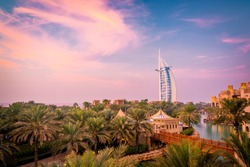 Amazing Cityscape with beautiful park with palm trees and hotels on a sunset in Dubai, UAE