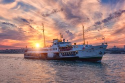 Amazing color sunset over Bosphorus with passenger boat (river tram) and sun, Istanbul, Turkey. Scenic travel background