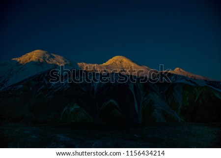Amazing colorful sunrise over mountain with rocks and ice in Tian Shan mountains in Central Asia near Almaty in cloudy weather. Best place for active life, climbing, hiking and trekking in Kazakhstan.