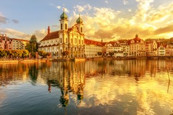 Amazing colorful sunset city center of Lucerne of Lake Lucerne in Central Switzerland. Jesuitenkirche or Jesuit Church of St. Francis Xavier reflects on Reuss river. Famous landmark of historical city