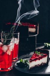 Amazing composition with strawberry cheesecake and strawberry drink with rosemary. Only part of the cheesecake in focus and a particle of a glass of drink.