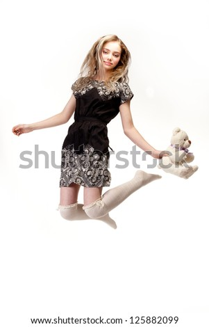 Amazing cute girl jumping with a teddy bear in her hand.