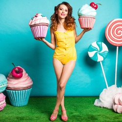 Amazing cute young pretty girl on the turquoise background holding a Huge sweets, Cake, candy, bright yellow body dresses, perfect makeup and hairstyle, fashionable Pin up girl, cool, smiling
