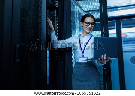 Amazing day. Happy beautiful woman working in a server cabinet and holding her laptop Foto stock ©