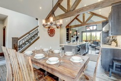 Amazing dining room near modern and rustic luxury kitchen with vaulted ceiling and wooden beams, long island with white quarts countertop and dark wood cabinets.