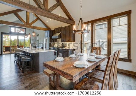 Amazing dining room near modern and rustic luxury kitchen with vaulted ceiling and wooden beams, long island with white quarts countertop and dark wood cabinets. Foto stock ©
