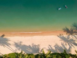 Amazing drone view of coast with tropical trees casting shadows on turquoise water of sea during sundown