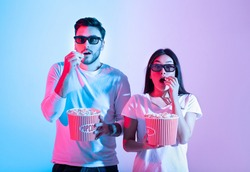 Amazing entertainment, leisure time together and cinema with modern technology. Surprised calm young guy and lady in 3d glasses eating popcorn and watching movie, in neon, studio shot, free space