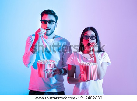 Amazing entertainment, leisure time together and cinema with modern technology. Surprised calm young guy and lady in 3d glasses eating popcorn and watching movie, in neon, studio shot, free space Photo stock ©