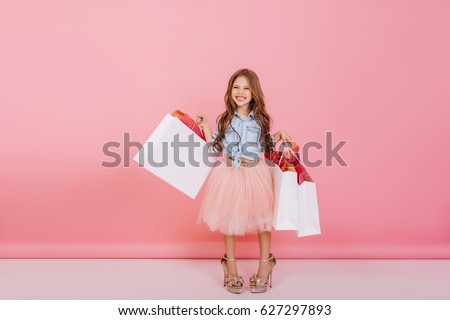Amazing excited happy girl in tulle skirt expressing to camera with white packages in hands isolated on pink background. Young shopper in mama`s shoes with presents, brightful emotions