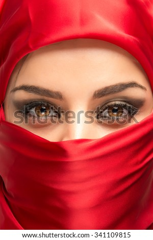 Amazing eyes from veileg young arabian woman in red scarf