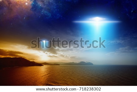 Amazing fantastic background - extraterrestrial aliens spaceship fly above sunset sea, ufo in red glowing sky. Elements of this image furnished by NASA