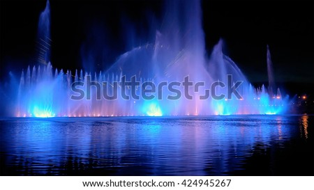 Amazing fantastic colorful fountain with bright illumination on the water pond or river with beautiful reflection at the evening or night. Beauty urban recreational concept. #424945267