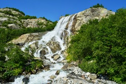 Amazing fast waterfall among high beautiful mountains, rocks and green trees and grass. Caucasus mountain, Russia.