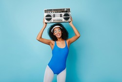 Amazing fitness girl enjoying music on blue background. Happy african young woman with boombox doing exercises.