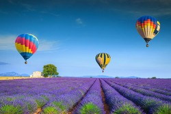 Amazing flowery summer landscape. Flying colorful hot air balloons over the purple fragrant lavender fields, Valensole, Provence, France, Europe. Travel and recreation concept